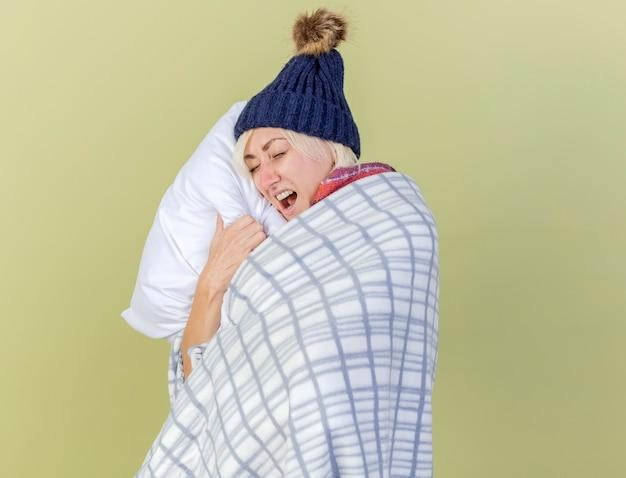 복사 공간 올리브 녹색 벽에 고립 된 격자 무늬 포옹 베개에 싸여 겨울 모자와 스카프를 착용 짜증이 젊은 금발의 아픈 슬라브 여자