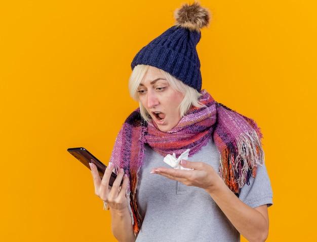 La giovane donna slava malata bionda infastidita che indossa il cappello e la sciarpa di inverno guarda