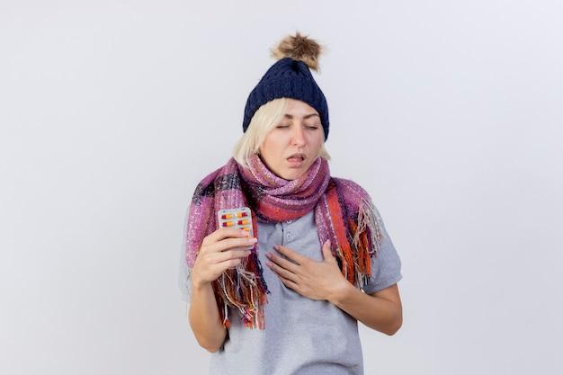 Раздраженная молодая блондинка больная женщина в зимней шапке и шарфе кладет руку на грудь и держит упаковку медицинских таблеток, изолированную на белой стене