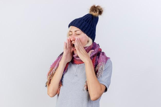 冬の帽子とスカーフを身に着けているイライラする若い金髪の病気の女性は、白い壁に隔離された顔の近くで手をつないで舌を突き出します