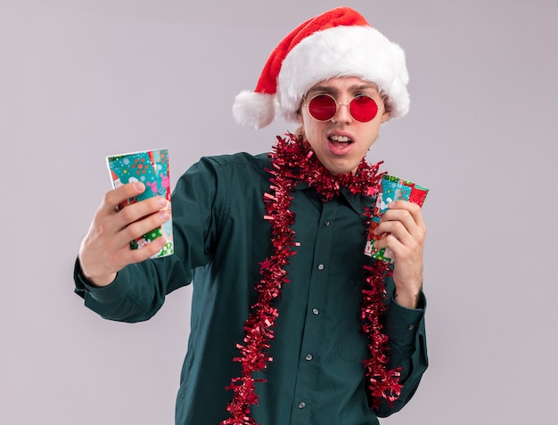 Annoyed young blonde man wearing santa hat and glasses with tinsel garland around neck holding plastic christmas cups stretching out one looking at it isolated on white background