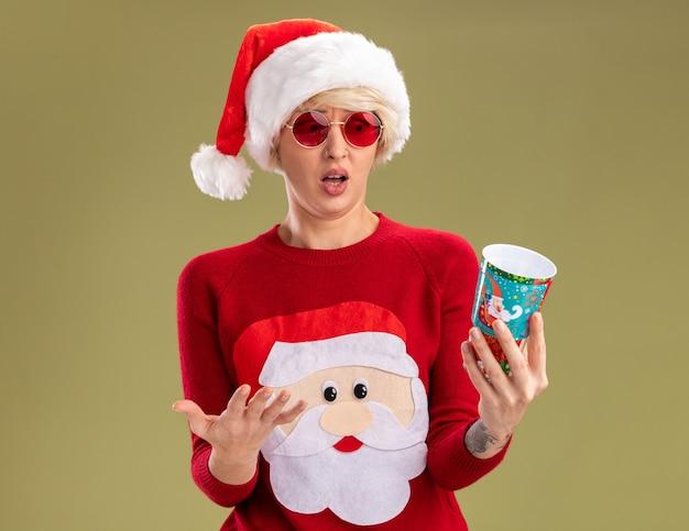 Раздраженная молодая блондинка в рождественской шапке и рождественском свитере санта-клауса в очках держит и смотрит на пластиковый рождественский стаканчик, показывая пустую руку, изолированную на оливково-зеленом фоне