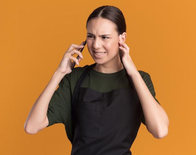 제복을 입은 짜증이 난 젊은 갈색 머리 이발소 소녀는 귀를 닫고 오렌지 쪽을보고 전화 회담