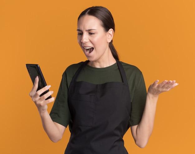 La giovane ragazza barbiere bruna infastidita in uniforme tiene la mano aperta tenendo e guardando il telefono isolato sulla parete arancione con spazio di copia