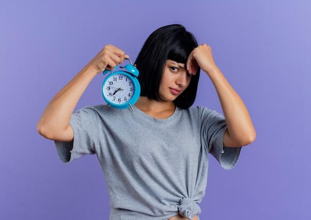 짜증이 젊은 갈색 머리 백인 여자 알람 시계를 보유하고 복사 공간이 보라색 배경에 고립 이마에 손을 넣습니다