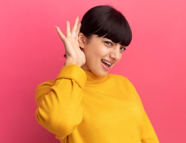La giovane ragazza caucasica castana infastidita tiene la mano dietro l'orecchio che guarda l'obbiettivo sul colore rosa