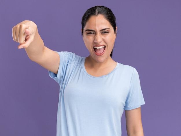 紫のカメラを見て、指しているイライラする若いブルネットの白人の女の子