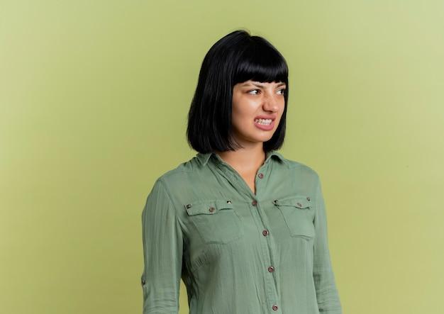 La giovane ragazza caucasica castana infastidita esamina il lato isolato su fondo verde oliva con lo spazio della copia