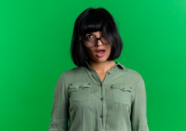 Giovane ragazza caucasica castana infastidita in vetri ottici rotolando gli occhi isolati su priorità bassa verde con lo spazio della copia