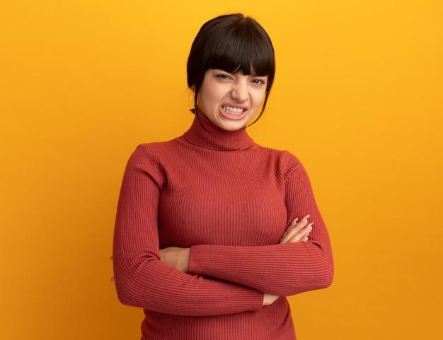 Раздраженная молодая кавказская девушка брюнетка стоит со скрещенными руками, изолированными на оранжевой стене с копией пространства