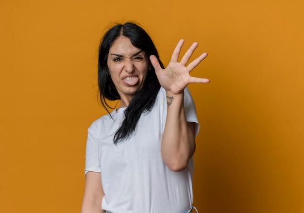 짜증이 젊은 갈색 머리 백인 여자 혀를 튀어 나와 오렌지 벽에 고립 된 손을 제기
