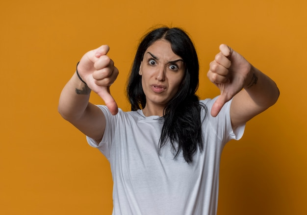 Infastiditi giovane ragazza bruna caucasica pollice in giù isolato sulla parete arancione