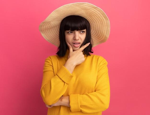 Раздраженная молодая брюнетка кавказская девушка в пляжной шляпе держит подбородок и смотрит в сторону