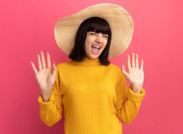 Раздраженная молодая кавказская девушка брюнетка в пляжной шляпе стоит с поднятыми руками на розовом