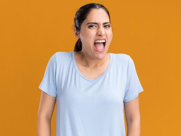 Раздраженная молодая брюнетка кавказской девушки кричит на кого-то на оранжевом