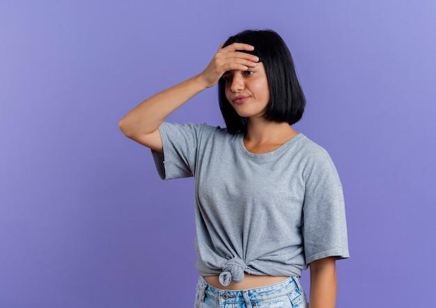 La giovane donna caucasica castana infastidita mette la mano sulla fronte che esamina il lato isolato su fondo viola con lo spazio della copia