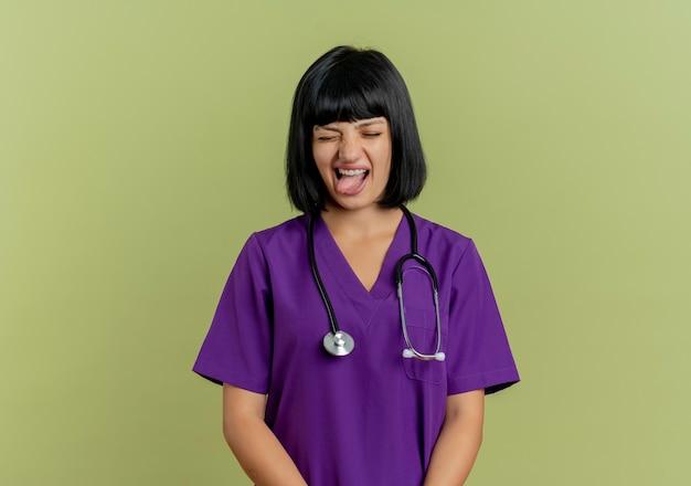 Раздраженная молодая брюнетка женщина-врач в униформе со стетоскопом высовывает язык на оливково-зеленом фоне с копией пространства