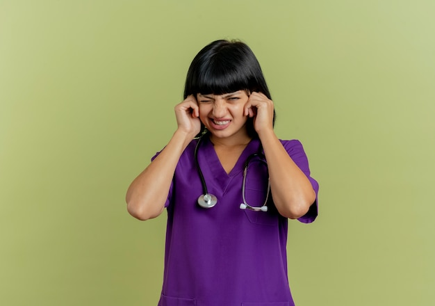 Infastidito giovane dottoressa bruna in uniforme con lo stetoscopio chiude le orecchie con le mani isolate su sfondo verde oliva con lo spazio della copia