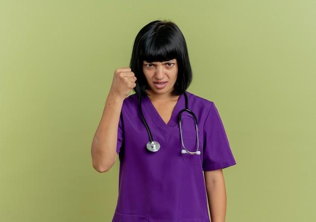 Il giovane medico femminile castana infastidito in uniforme con lo stetoscopio tiene il pugno che guarda l'obbiettivo isolato su fondo verde oliva con lo spazio della copia