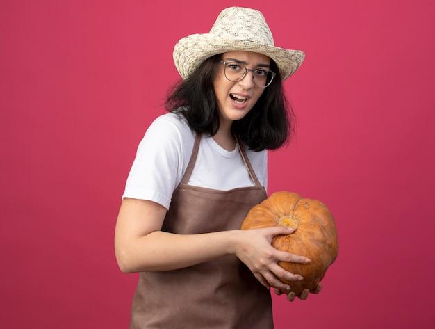 광학 안경과 원예 모자를 쓰고 제복을 입은 화가 젊은 갈색 머리 여성 정원사는 호박 분홍색 벽에 고립 된 보유