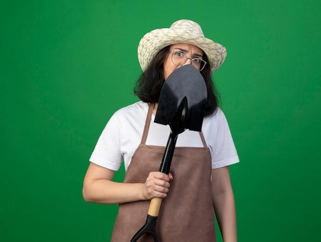 光学ガラスと制服を着たガーデニング帽子をかぶったイライラした若いブルネットの女性の庭師は、緑の壁に隔離されたスペードを保持し、正面を見る