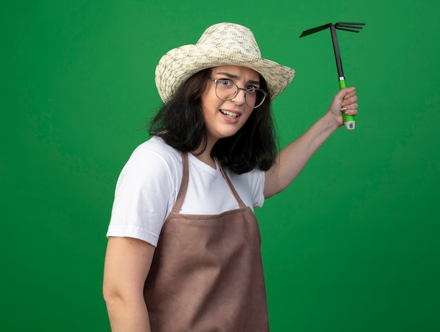 光学ガラスと制服を着たガーデニング帽子でイライラする若いブルネットの女性の庭師は、緑の壁に分離されたくわ熊手を保持します