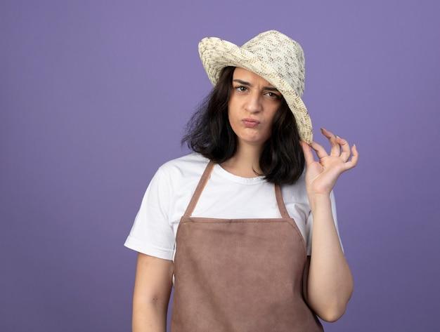Giardiniere femminile castana giovane infastidito in uniforme che indossa e che tiene il cappello di giardinaggio isolato sulla parete viola