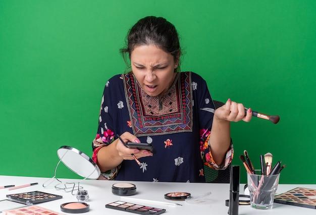 Раздраженная молодая брюнетка девушка сидит за столом с инструментами для макияжа, держит кисти для макияжа и смотрит на телефон, изолированный на зеленой стене с копией пространства