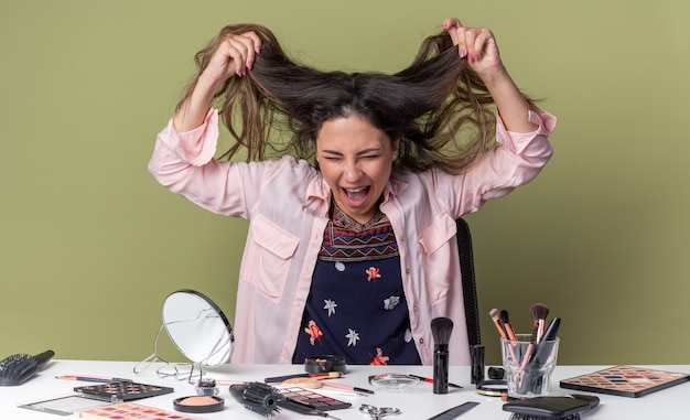 Annoyed young brunette girl sitting at table with makeup tools holding her hair