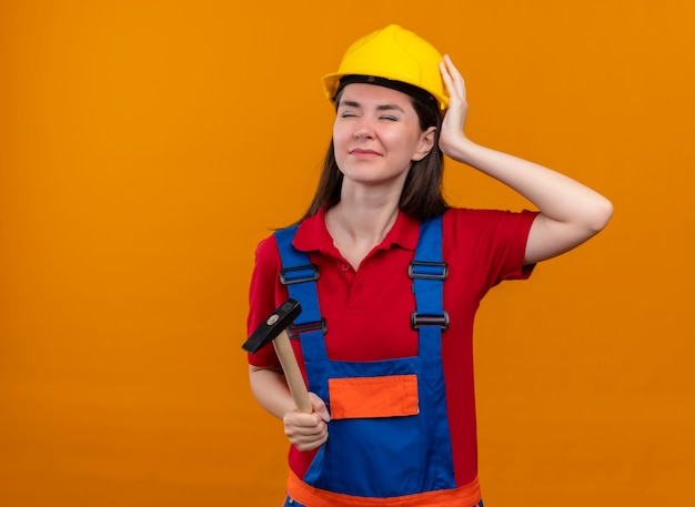 La giovane ragazza infastidita del costruttore tiene il martello e mette la mano sulla testa su fondo arancio isolato con lo spazio della copia