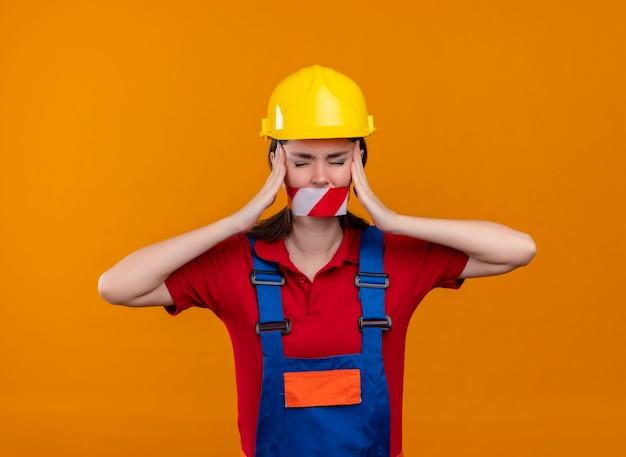 La bocca infastidita della ragazza giovane costruttore sigillata con nastro adesivo di avvertenza tiene la testa con entrambe le mani su sfondo arancione isolato