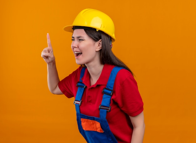 イライラする若いビルダーの女の子が上を向いて、孤立したオレンジ色の背景で横に見えます