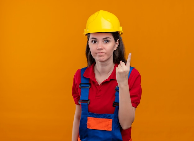La giovane ragazza infastidita del costruttore mostra un gesto del dito su fondo arancio isolato con lo spazio della copia