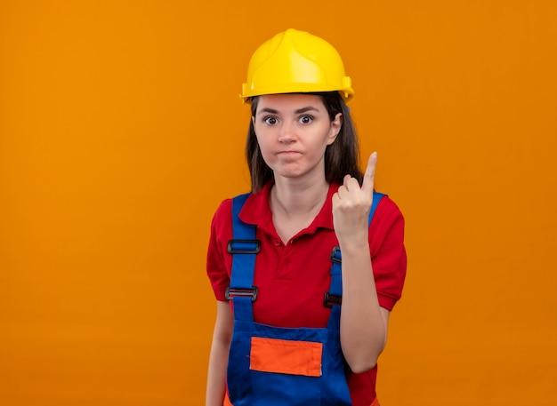 イライラする若いビルダーの女の子は、コピースペースで孤立したオレンジ色の背景に1本の指のジェスチャーを示しています