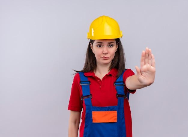 La giovane ragazza infastidita del costruttore mostra il gesto di arresto su fondo bianco isolato con lo spazio della copia