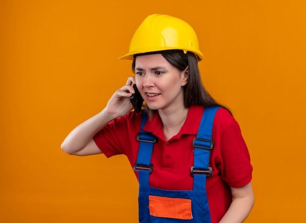 コピースペースと孤立したオレンジ色の背景で電話で話しているイライラする若いビルダーの女の子