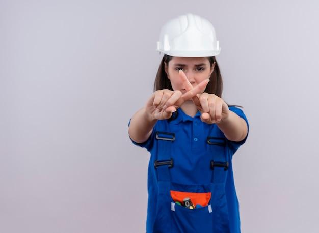 白い安全ヘルメットと青い制服のジェスチャーでイライラする若いビルダーの女の子は、コピースペースで孤立した白い背景に指でありません