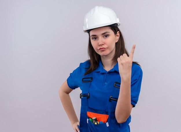 白い安全ヘルメットと青い制服を着たイライラした若いビルダーの女の子は、コピースペースで孤立した白い背景を指しています