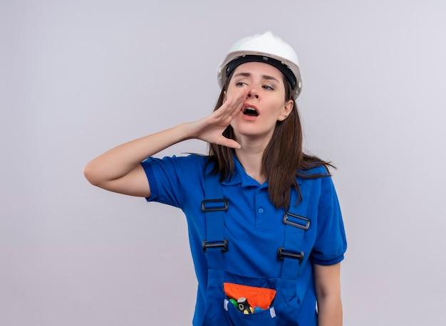 白い安全ヘルメットと青い制服を着たイライラした若いビルダーの女の子は、コピースペースで孤立した白い背景に誰かを呼び出すふりをします