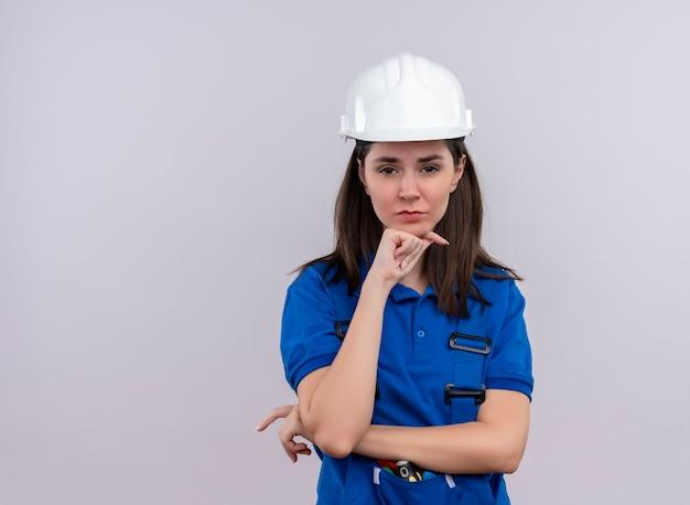 白い安全ヘルメットと青い制服を着たイライラする若いビルダーの女の子は、あごに手を置き、コピースペースで孤立した白い背景の上のカメラを見る