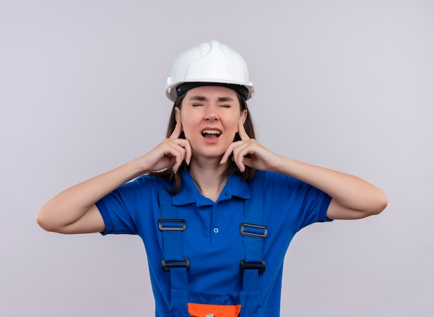 La giovane ragazza infastidita del costruttore con il casco di sicurezza bianco e l'uniforme blu tiene le orecchie con le dita su fondo bianco isolato con lo spazio della copia
