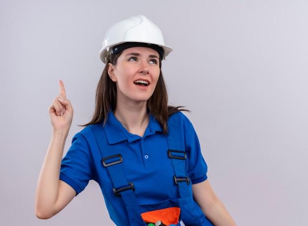 La giovane ragazza infastidita del costruttore con il casco di sicurezza bianco e l'uniforme blu indica in su e cerca su fondo bianco isolato con lo spazio della copia