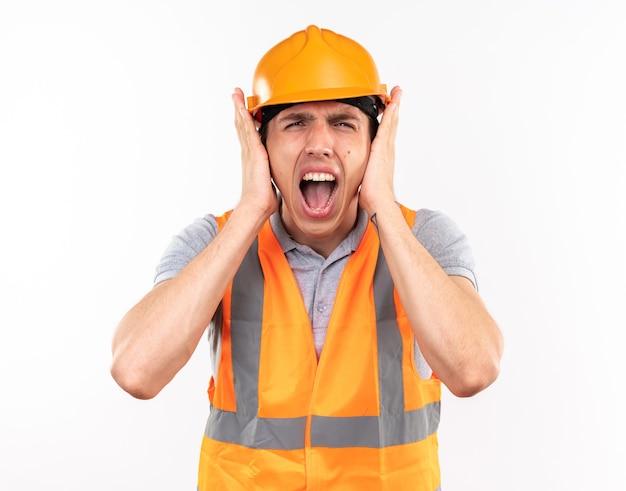 Infastidito giovane costruttore in uniforme ha coperto le orecchie