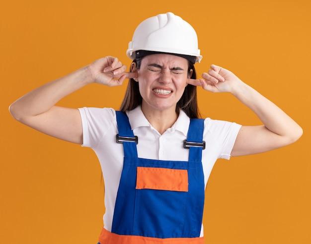 La giovane donna infastidita del costruttore in uniforme ha coperto le orecchie isolate sulla parete arancione