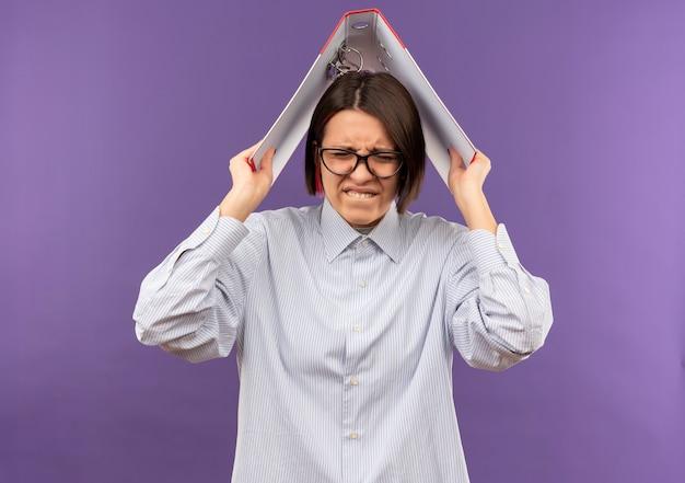 Ragazza giovane call center infastidita con gli occhiali che tiene cartella sulla testa isolata sulla porpora