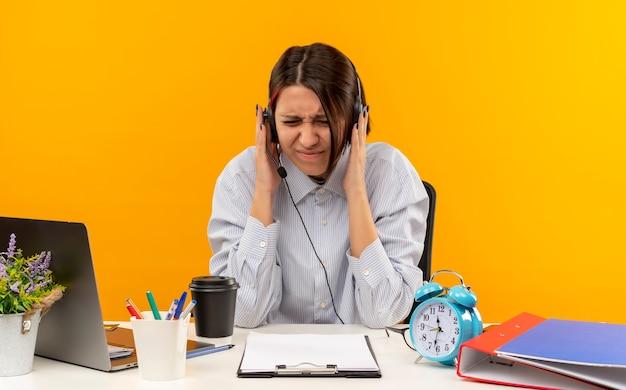 Infastiditi giovani call center ragazza indossa la cuffia avricolare seduto alla scrivania mettendo le mani sulla cuffia con gli occhi chiusi isolati su arancione