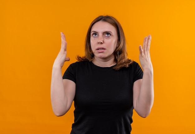 Annoyed young casual woman raising hands looking up on isolated orange space with copy space