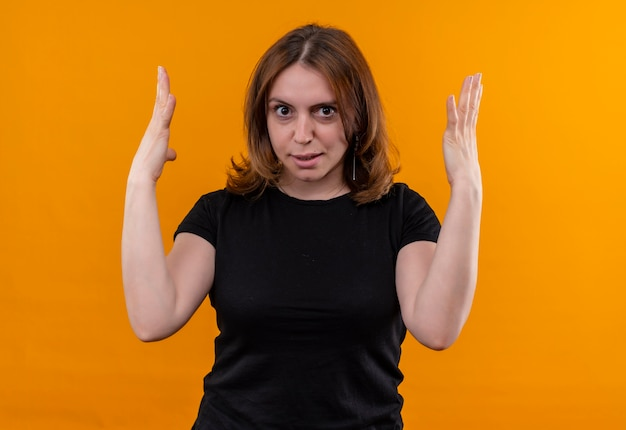 Annoyed young casual woman with raised hands on isolated orange space