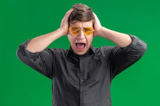彼の頭を保持しているサングラスでイライラする若い白人の少年