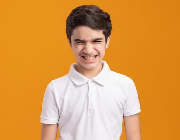 Раздраженный молодой кавказский мальчик показывает зубы